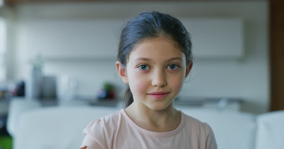 Portrait of a little girl with blue eyes looking in the camera on living room background. Shot with RED camera in 8K. Concept of childhood, kids protection, daughter, happy family   Shutterstock HD Video #1020974440