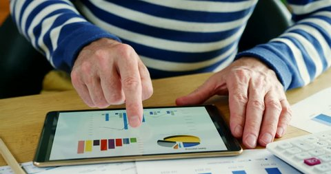 Close up of casual businessman swiping through financial charts on a digital tablet. Businessman is referencing financial graphs