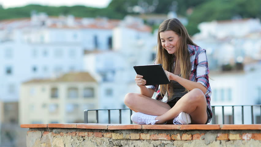 Happy teenage girl using a tablet sitting on a ledge in a coast town on vacation