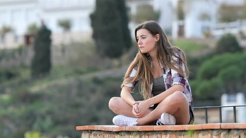 Sad teenage girl complaining sitting on a ledge in a town on vacation