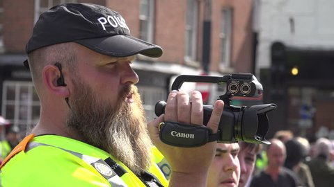 Worcester, United Kingdom (UK) - 09 01 2018: A beard police surveillance officer films with a video camera