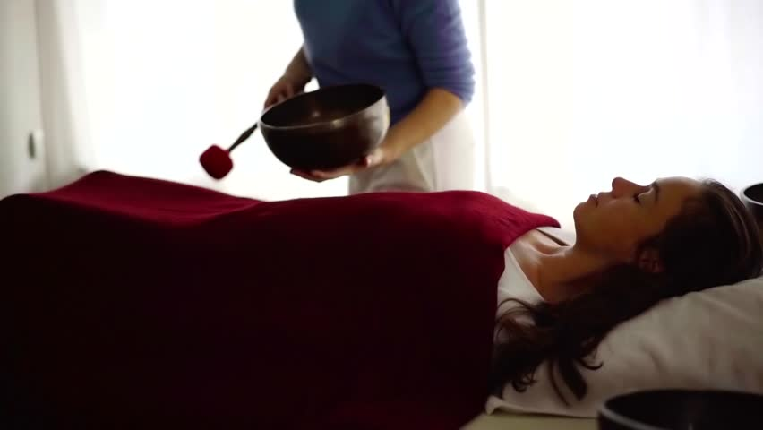 Woman lying under the red towel on a table on singing bowl massage in spa. | Shutterstock HD Video #1021049980