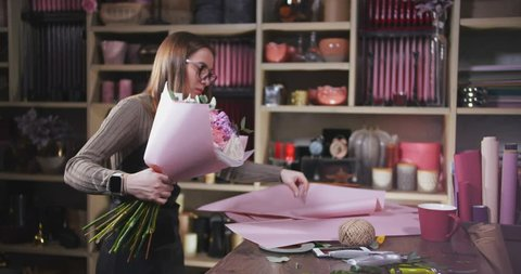 Female flower shop seller packing a bouquet in wrapping paper for customer, flower delivery, small business concept
