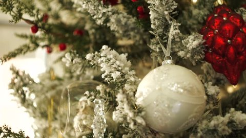 Christmas tree with artificial snow decorated with red and white christmas tree toys. Christmas tree balls, transparent glass toys, artificial berries and shinning lights on christmas tree, close-up.