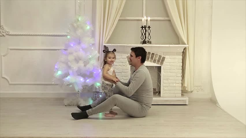 Dad throws his daughter with two tails on the background of a fireplace and a Christmas Tree | Shutterstock HD Video #1021144390