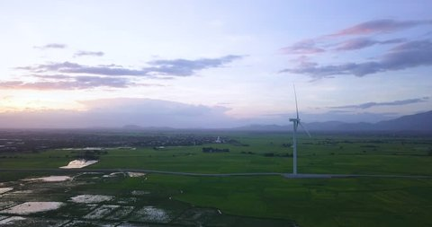 Wind turbine farm and agricultural fields on a summer day. High-quality stock video footage wind turbine in a green field - Energy Production with clean and Renewable Energy. Phan Rang, Vietnam