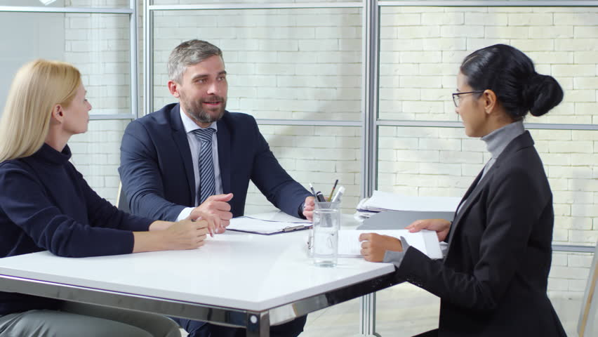 Tracking shot of young woman in glasses and formalwear sitting opposite businesswoman and businessman conducting job interview. She is giving them her CV and talking about skills and experience | Shutterstock HD Video #1021147420