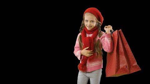 A little girl with pigtails in a red knitted hat and scarf carries shopping bags or gifts by throwing them on her shoulder and shows the class smiling, winter shooting on an isolated background