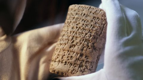 A person with white gloves check out an ancient cuneiforme.  One of the earliest Sumerian systems of writing,