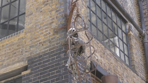 A skeleton inside an iron cage hanging off the wall.