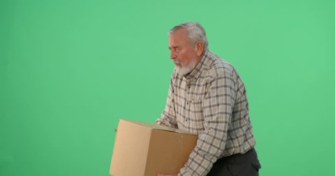 Senior adult male lifts a heavy box and experiences severe back pain; 4k footage shot on chroma key green background