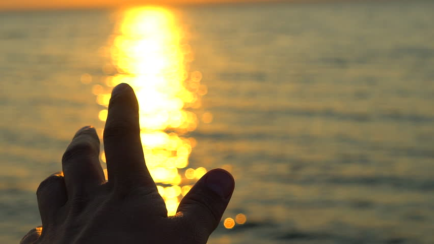 Man hand at sunset on sea, ocean beach. A man's hand in sun's rays on background sea water in nature. summer time glare of sun through fingers Tourism travel traveler happy holiday summer summertime