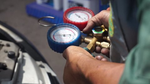 Car Air Conditioner Check Service, System Refrigerant Recharge Or Fill, Leak Detection. Auto Mechanic Uses a Pressure Gauge On The Air Compressor, Liquid Air Pressure.