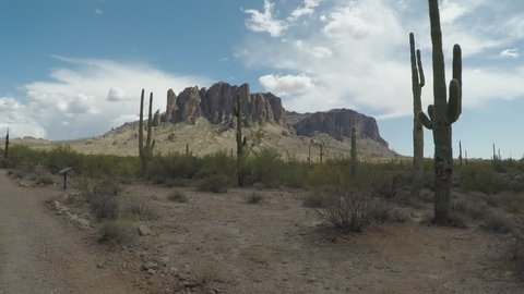 Apache Junction, AZ / USA - July 10, 2018: Shot of Saguaro Cactus and Superstition Mountains. Nature clip provides classic desert scene and Southwest imagery.