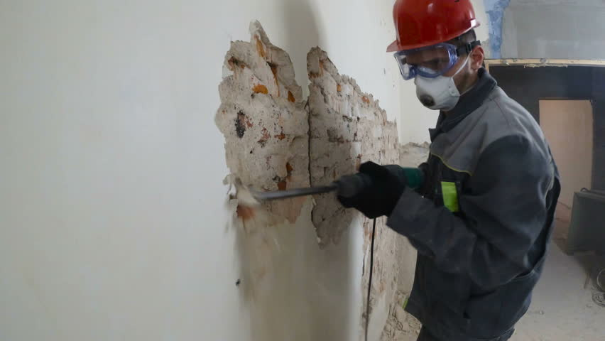 Worker in protective suit demolishes plaster wall. Dirty, hard work. Personal protective equipment. Helmet, respirator and goggles. | Shutterstock HD Video #1021290460