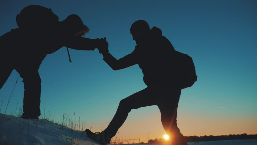 Teamwork business travel silhouette concept. two hikers winter snow tourists climbers climb to the top of mountain . overcoming hardships the path lifestyle to victory, teamwork, important points in | Shutterstock HD Video #1021321300