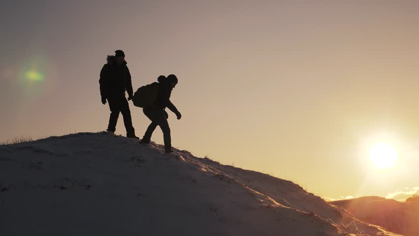 Teamwork silhouette business travel concept. two hikers tourists slips falls come down from climbers climb to the top of the mountain. overcoming hardships the path to victory, teamwork, important | Shutterstock HD Video #1021321330