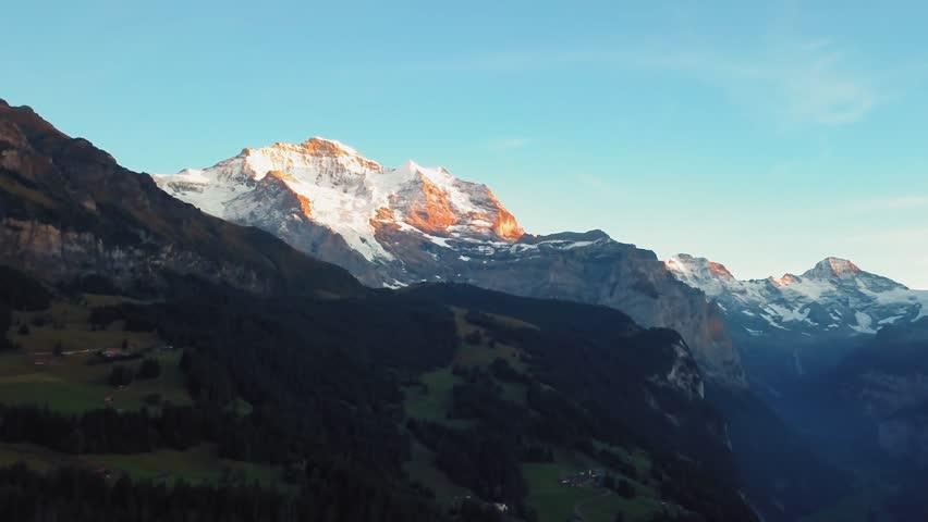 Sun sets over Swiss alps Jungfrau peak and Wengen town. Aerial pull back, 4k. | Shutterstock HD Video #1021331560