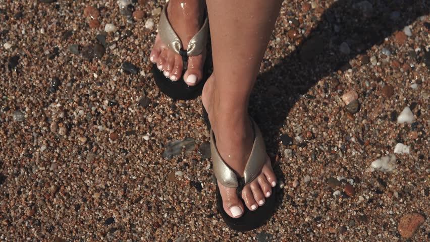Shot from above of beautiful woman's feet in flip-flops walking across sand beach in summer. Woman enjoying lovely walk on beach in hot summer. | Shutterstock HD Video #1021361680