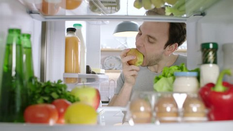 A man opening a fridge looking for a healthy snack takes an apple. POV from inside the refrigerator.
