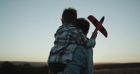 Closeup hugging dad with his son, and holding a big airplane watching sunset.