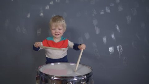 Concept of music. Happy Caucasian childish drummer in multicolored T-shirt plays on new drum set with drum sticks in his hands. Parents bought children's drum as birthday present. Funny blondie kid