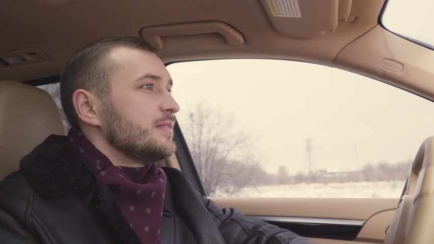 Young bearded businessman in winter coat drives a premium car on his way to work. Busy days. | Shutterstock HD Video #1021409230