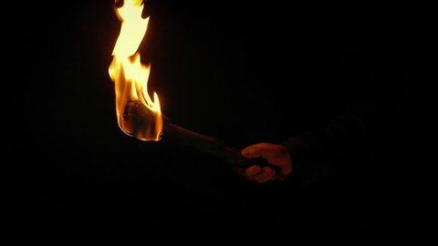 Man Holds Up Fire Torch At Night