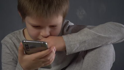 Cute boy from school for children with poor eyesight look at smartphone screen. Shallow focus