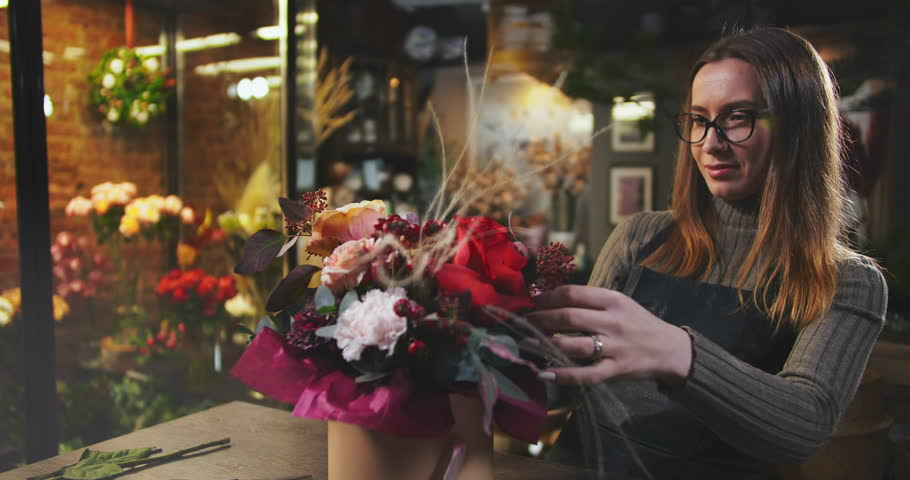 Caucasian woman completing beautiful bouquet in flower shop. Flower sale and delivery. Small business concept