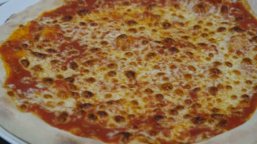 Inside italian pizzeria, cooked  pizza is cut with a round pizza knife closeup #1021475050