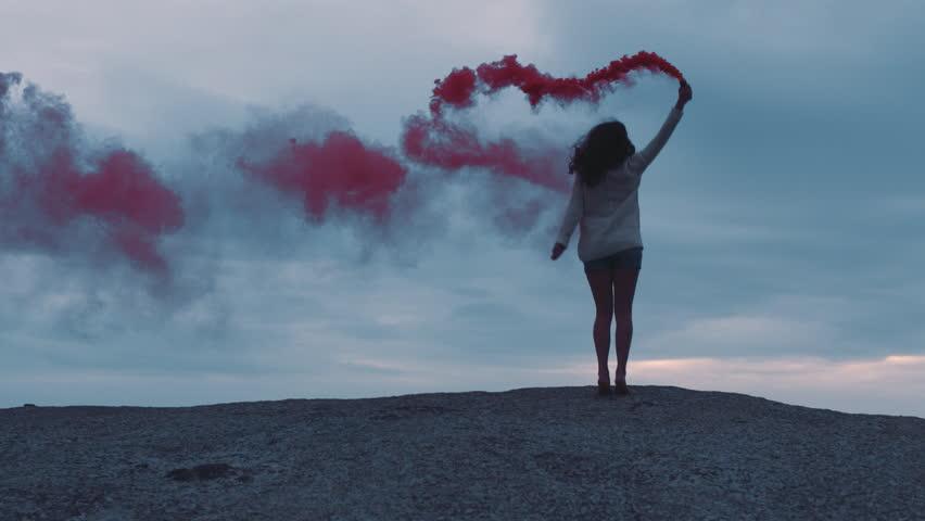 Young woman playing with pink smoke grenade dancing on seaside beach enjoying freedom | Shutterstock HD Video #1021477180