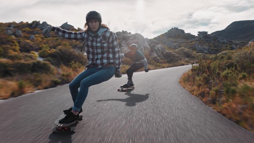 Young happy woman riding longboard friends skating enjoying cruising downhill on beautiful countryside road having fun using skateboard wearing protective helmet | Shutterstock HD Video #1021486180