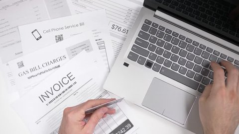 The information on the bills are fake, placeholder name is use. Paying bills using a laptop computer. Online utility bills payment concept.