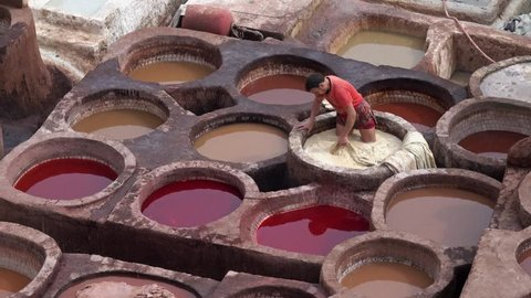 FEZ, MOROCCO - CIRCA FEB 2018: Men working as a tanner in old tanks at leather tanneries with color paint. Ancient medina, Chouara Tannery, Fes el Bali