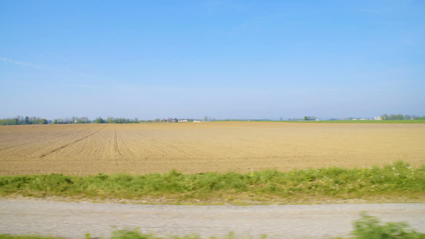 Car side window view of road next to a farm land HD. Wide shot of the field in focus from person view inside the car. Bright brown field and blue sky above. | Shutterstock HD Video #1021557820