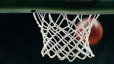 A basketball tournament. Throwing a ball in a basketball hoop. The ball gets right in target. Slow motion
