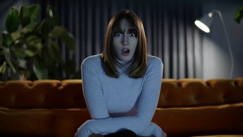 Young woman sitting on a cozy sofa at home at night watching tv reacts to something on screen with a shocked and surprised expression on her face. Camera pushes in towards her.