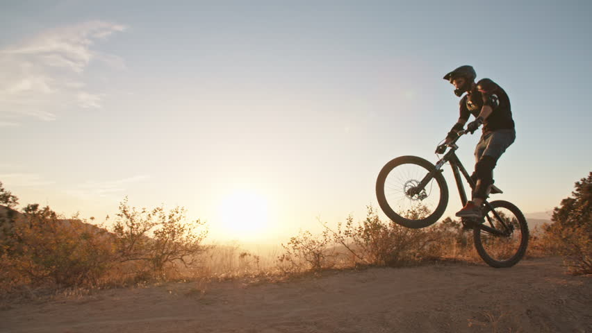 Cool mountain biker jumping at sunset, speeding up the trail, rushing down off road. Getting away from it all - activity, extreme #1021585630