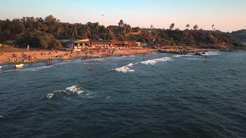 Aerial Drone Pulling Away Slowly 60fps from popular tourist Candolim beach area in North Goa