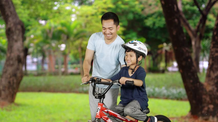 Happy little boy learns to ride bicycle with his father at the park. Shot in 4k resolution | Shutterstock HD Video #1021634200