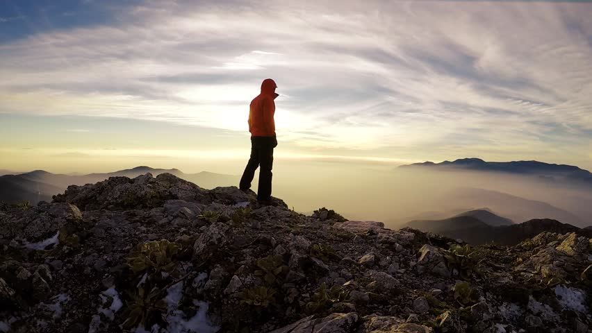 Young male climber, summit of the mountain, above the clouds. Sunset in a winter season. Kemalpasa / Izmir / Turkey