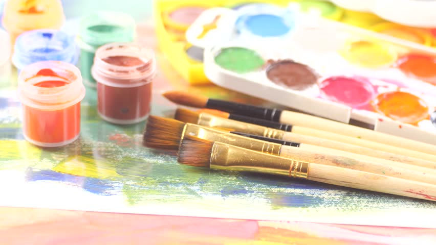 Paint brushes and watercolor paints in motion on the table | Shutterstock HD Video #1021693660