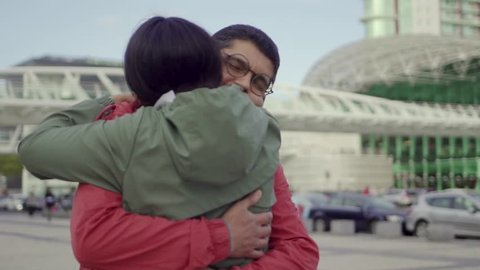 Joyful hindu spouse hugging outdoor. Happy young couple embracing near terminal. Happiness concept