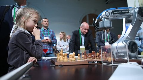 ST. PETERSBURG, RUSSIA - DECEMBER 27, 2018: Robot playing chess with a girl in Exhibition Hall Manege during World Rapid and Blitz Chess Championship. The robot simultaneously plays on 3 chess boards
