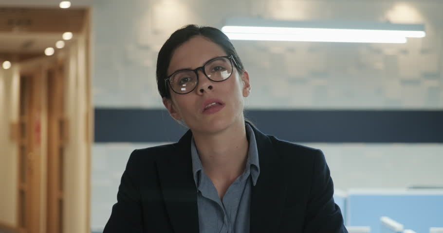 Portrait of Unhappy Strong Serious Young White Businesswoman in Office a strong, independent female professional posing at work looking at the camera with a serious expression on her face. | Shutterstock HD Video #1021706170