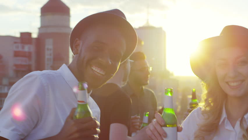 Young african american man and beautiful caucasian woman in fedora hats holding beer bottles, smiling and looking at camera while dancing together at rooftop party with friends
