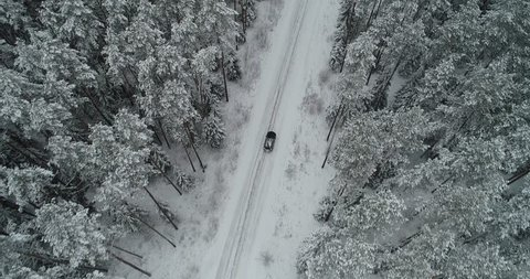 Aerial view of car driving on winter country road through snow covered forest. Smooth stable video footage