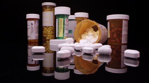 Prescription drugs and opioids on table top viewing up close and moving into bottle.