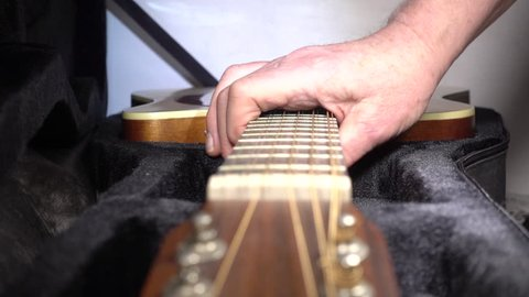 Slow motion close POV shot of a man's hand lifting a traditional acoustic guitar out of its soft, padded, case, then shutting the lid.